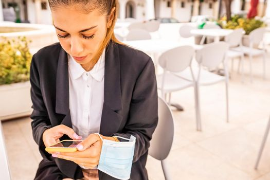 Young woman self entrepreneur texting on smartphone sitting at bar dehors with holding protective face mask in hand. Freelance girl taking breakfast at hotel cafe using technology. New normal habits