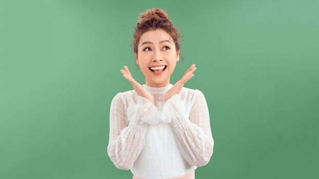 Photo portrait of excited woman with open mouth holding hands near face isolated on green colored background