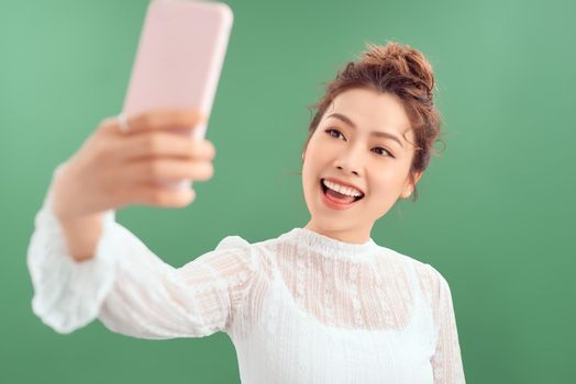 Lovely young alluring woman posting photo online, video-calling friend, holding smartphone raised as taking selfie, tilt head making cute expression