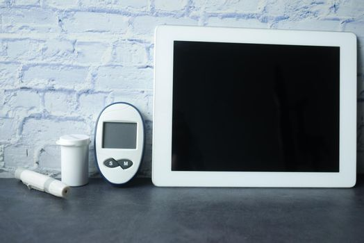 top view of digital tablet and diabetic measurement tool on table