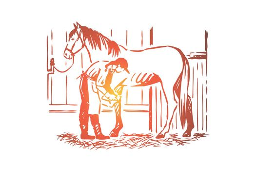 Young woman checking stallion horseshoe, equine care, female farmer in apron, purebred mare in stable