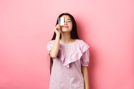 Shopping. Cute candid woman smiling, showing plastic credit card on face, standing in dress against pink background
