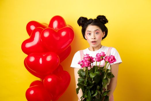 Happy Valentines day. Surprised asian girl receive bouquet of pink roses from lover, looking with awe at camera, standing near red heart balloons, yellow background