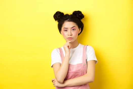 Suspicious asian girl looking at camera and thinking, stare with disbelief, standing with makeup on yellow background