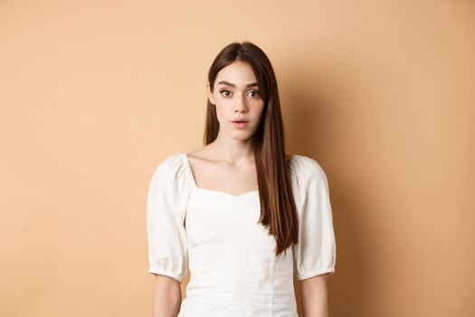 Shocked and startled young woman freeze in awe, open mouth and look at camera amazed, standing in dress on beige background