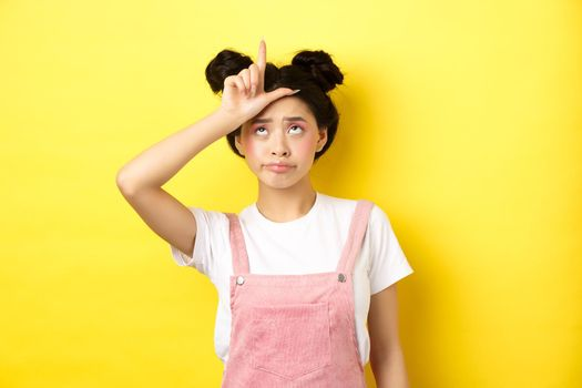 Sad girl showing loser sign on forehead and sulking upset, feeling disappointed in herself, standing on yellow background