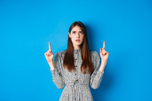 Confused attractive woman in dress frowning, pointing fingers up and looking puzzled, cant understand something, stare at strange thing, blue background