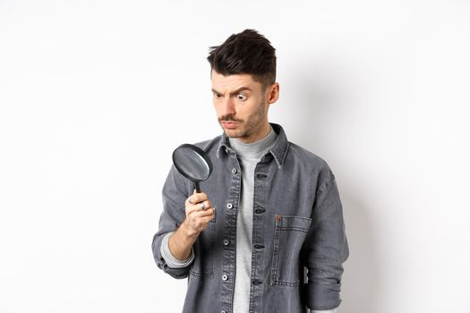 Serious man investigating, looking down with magnifying glass, stare serious, standing on white background