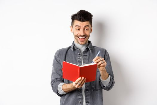 Excited guy writing in planner and smiling, writing down ideas in journal or diary, standing on white background