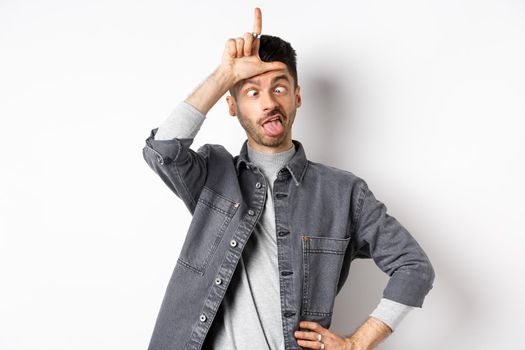 Funny young man making faces and showing tongue with loser sign on forehead, squinting eyes, standing on white background