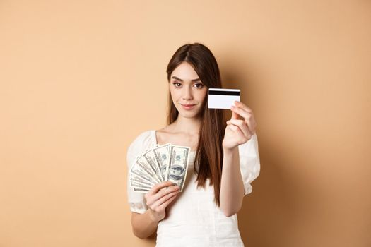 Young woman showing plastic credit card, prefer contactless payment instead of dollar bills, standing on beige background