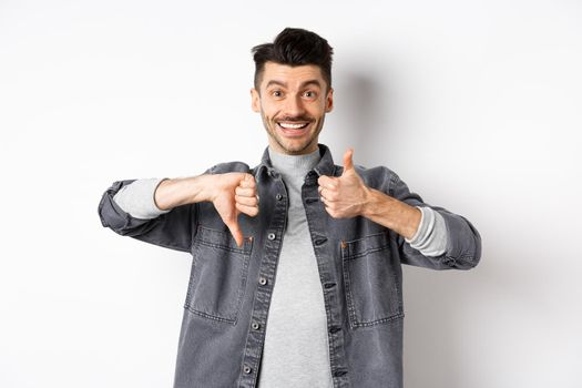 Happy smiling guy showing average gesture, thumbs down up, cant decide, judging something medium, standing on white background