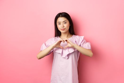 Valentines day concept. Beautiul japanese teen girl show heart gesture and smiling cute, express love and sympathy to lover, standing in romantic dress on pink background