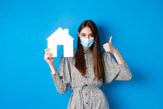 Real estate, covid-19 and pandemic concept. Candid woman in medical mask showing thumb up and paper house cutout, reanting apartment, standing on blue background