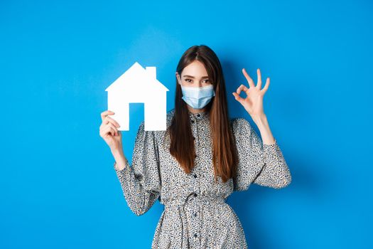 Real estate, covid-19 and pandemic concept. Candid woman in medical mask showing okay sign and paper house cutout, selling property, standing on blue background