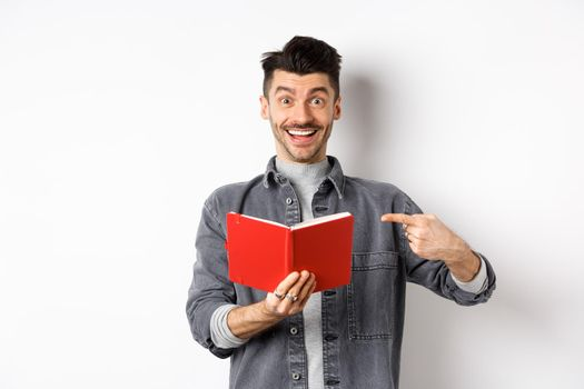 Happy smiling guy pointing at red planner, showing good journal or book, standing on white background