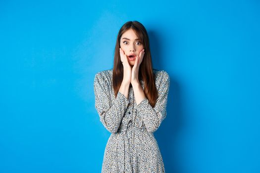 Shocked cute woman gasping amazed, drop jaw and stare with disbelief, standing in dress on blue background