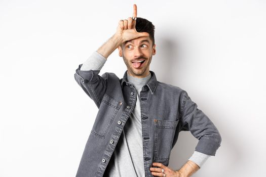 Funny guy mocking person, showing tongue and loser sign on forehead, making fun of lost team, standing on white background