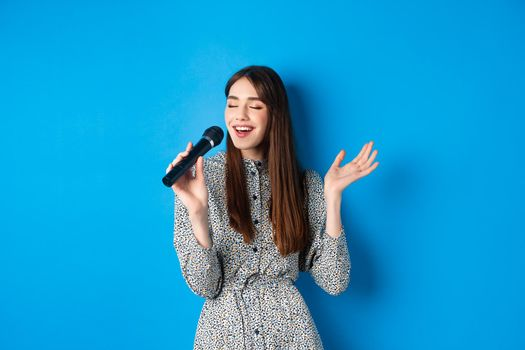 Beautiful candid girl singing in microphone, close eyes and smile carefree, sing at karaoke. Leisure and hobbies concept