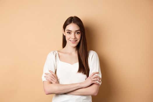 Smiling candid girl in dress cross arms on chest, looking like professional, standing confident on beige background
