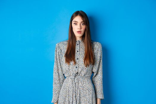 Shocked caucasian woman with long hair, wearing dress, gasping and standing in stupid against blue background, stare with disbelief