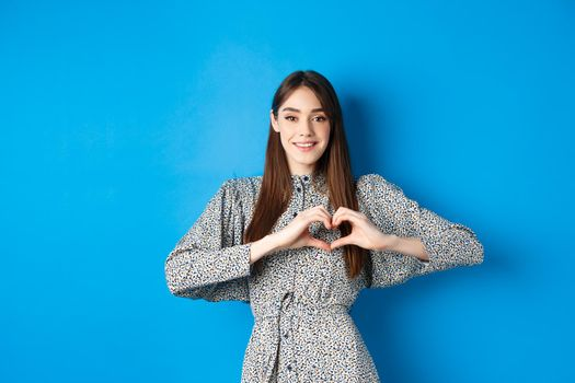 Pretty girl in romantic dress showing I love you heart gesture, smiling at camera, express sympathy and romance, standing on blue background