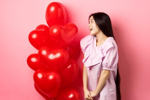 Romance and love concept. Romantic asian girl looking with affection and sympathy at empty space, standing near red hearts balloons from lover, pink background