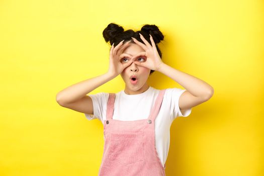 Excited asian teen girl look through hand binoculars aside, say wow and stare surprised, checking out advertisement, yellow background