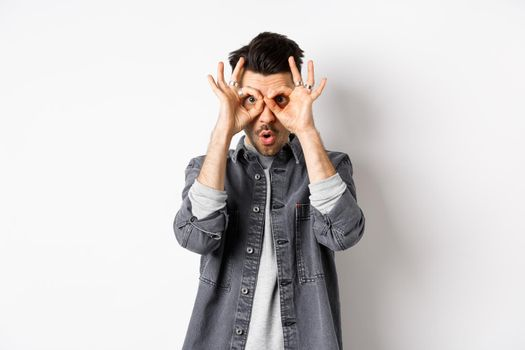 Funny guy look through hand binoculars, checking out awesome promo, say wow and stare at camera excited, standing on white background