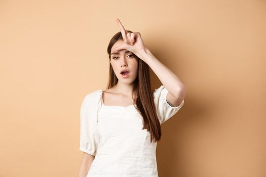 Confident woman mocking people with loser sign, being mean, standing on beige background