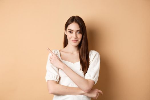 Smiling good-looking girl in white dress pointing aside, showing left logo and staring at camera confident, standing on beige background
