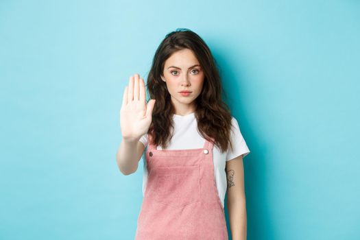 Young brunette woman with curly hairstyle, raising hand in block gesture, say stop or no, refuse bad offer, rejecting something, standing against blue background