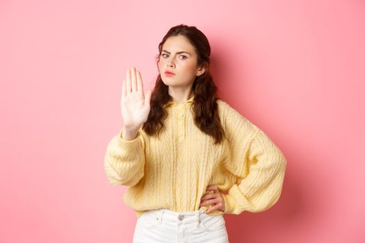 Angry and bossy young woman frowning, looking serious, showing block stop gesture, stretch out hand to say no, refuse something bad, forbid action, standing against pink background