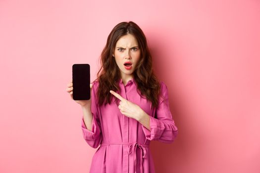 Technology concept. Angry girl points at her smartphone screen and staring judgemental at camera, demand answers or explanation, standing over pink background