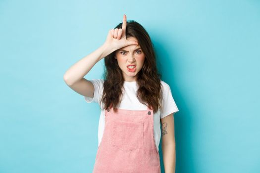 Sassy young woman despise her rival, showing loser gesture on forehead, making letter L with hand and staring with dismay at camera, standing against blue background