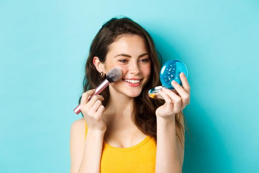 Beauty. Modern girl with candid smile applying make up with brush, looking in pocket mirror, standing over blue background