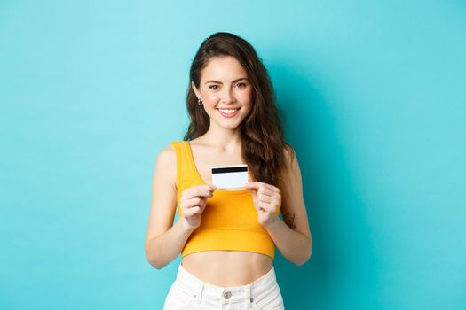 Shopping. Smiling good-looking woman in summer clothes, showing plastic credit card, looking confident, standing over blue background