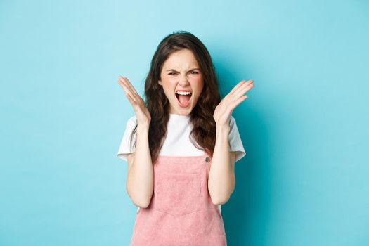 Angry and annoyed young woman screaming, frowning and looking outraged, shaking hands, stare frustrated and bothered, shouting at someone, standing over blue background