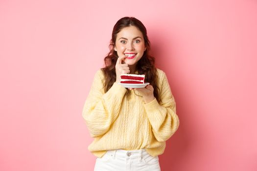 Image of excited girl thinking of eating delicious cake, biting finger from temptation and looking thoughtful at camera, think of calories in dessert, pink background