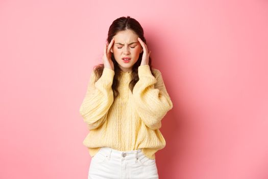 Young woman having terrible headache, touching head and grimacing from pain of migraine, need painkillers, standing against pink background