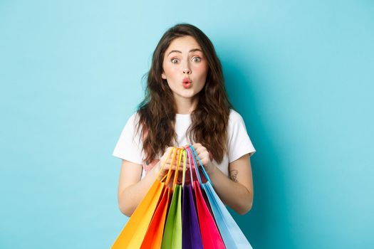 Portrait of excited young woman spot good discount offer in store and stare at camera, holding shopping bags, standing over blue background