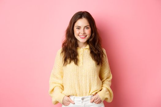 Portrait of good-looking young woman in sweater, holding hands in pockets, smiling and staring determined at camera, standing against pink background