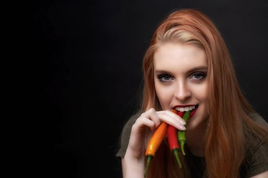 Attractive young woman is tasting colorful chili peppers