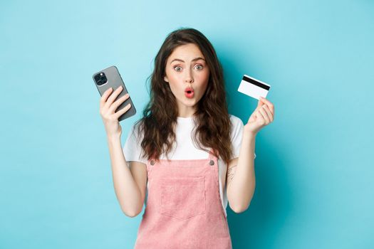 Surprised young woman say wow, stare excited at camera, holding mobile phone and plastic credit card, standing over blue background