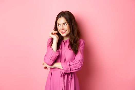 Coquettish caucasian woman with nice hairdo and spring dress, looking aside, left copyspace, smiling thoughtful, standing over pink background