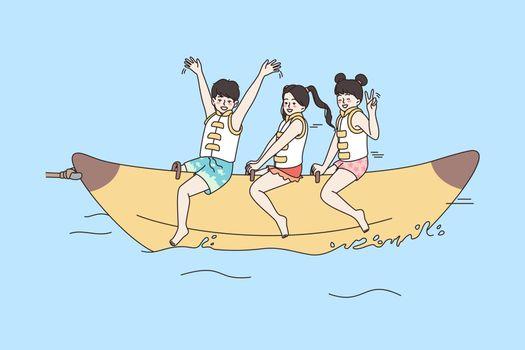 Overjoyed kids have fun ride banana boat at sea