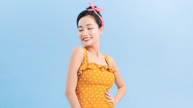 Asian woman in sleeveless yellow tone polka dot dress