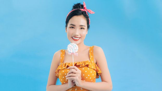 Portrait of pin-up woman 20s in vintage polka dot dress smiling while holding and eating colorful lollipop isolated over blue background