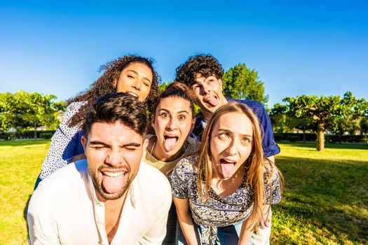 Group of silly young multiracial millennial friends making funny faces with tongue, open mouth, and squinting eyes posing for a portrait in city park. Live your life lightly while having fun in nature