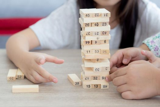Asian little girl playing game build wood toy with friends on table at home, children concentration and creative for learning, imagine and development and constructor, education and lifestyle concept.